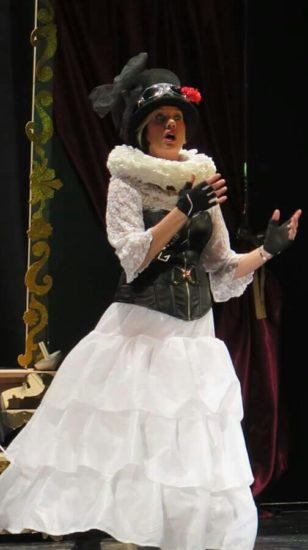 Una scena dello spettacolo. Una donna è inquadrata in figura intera e ripresa nell'atto di pronunciare qualcosa. Il vestito è composto di una lunga gonna a balze bianca e un corpetto nero sopra una camicia con maniche di merletto bianche anch'esse, su cui ricade un ampio girocollo dello stesso colore. A completare la figura, un cappello nero con un fiore rosso.