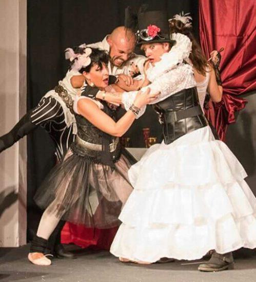Una scena dello spettacolo. Quattro personaggi, vestiti con abiti d'epoca, si azzuffano tra loro.