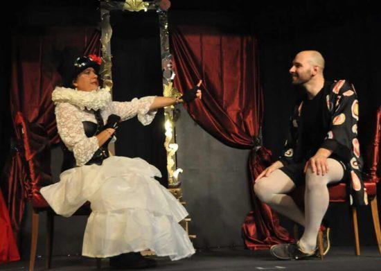Una scena dello spettacolo. Seduti l'uno di fronte all'altra, stanno un uomo e una donna, entrambi vestiti con abiti d'epoca. La donna, allungando il braccio verso l'interlocutore, sembra irritata, e opponendo l'indice  sembra mostrare l'intenzione di zittire l'uomo.