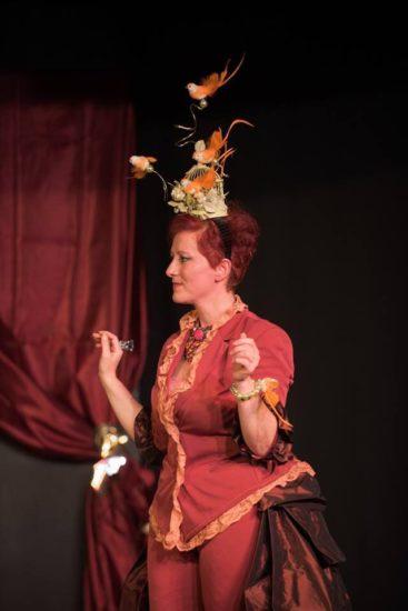 Una scena dello spettacolo. Un'attrice sul palco, inquadrata a mezzo busto vestita con abiti d'epoca, con un cappello ornato di uccellini arancioni